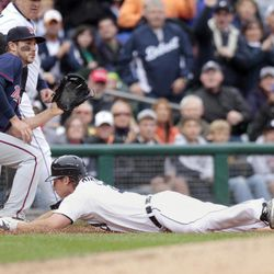 Detroit Tigers' Andy Dirks, right, dives into third base for a triple, beating the throw to Minnesota Twins third baseman Trevor Plouffe during the third inning of a baseball game Saturday, Sept. 22, 2012, in Detroit.