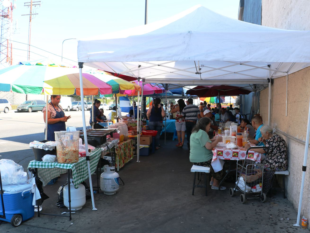 Salvadoran street market in front of Koreatown's Two Guys Plaza with stalls and cooked foods.