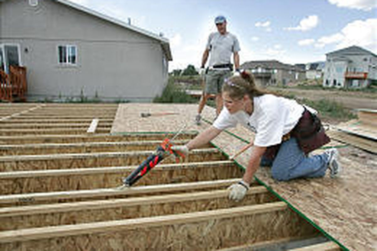 Chandler Morrison, foreground, of Oakley gets help from volunteer Pete Kowanko as she constructs a home through a progam that assists low-income families.