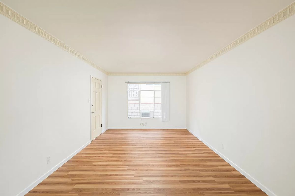 Empty room with white walls and a wood floor