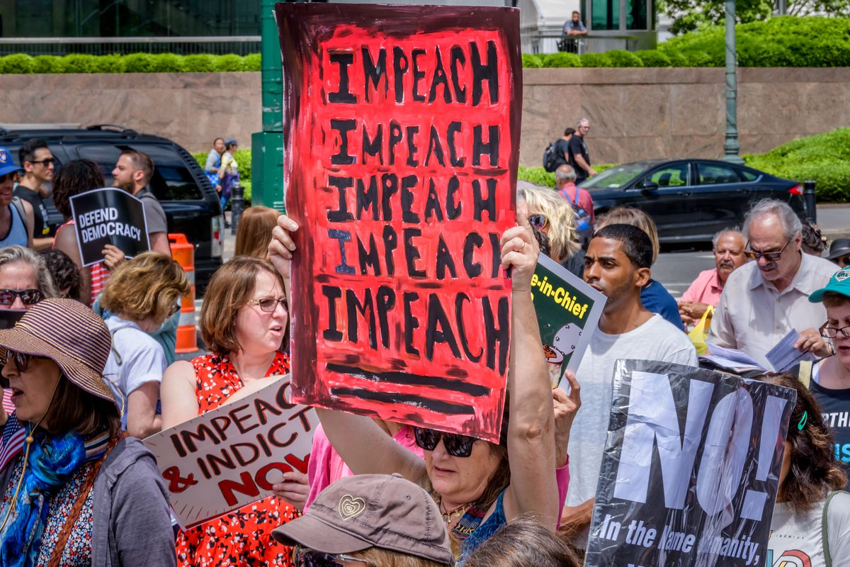 """New Yorkers hoist handmade signs; the largest is red and black, and says """"impeach"""" five times."""