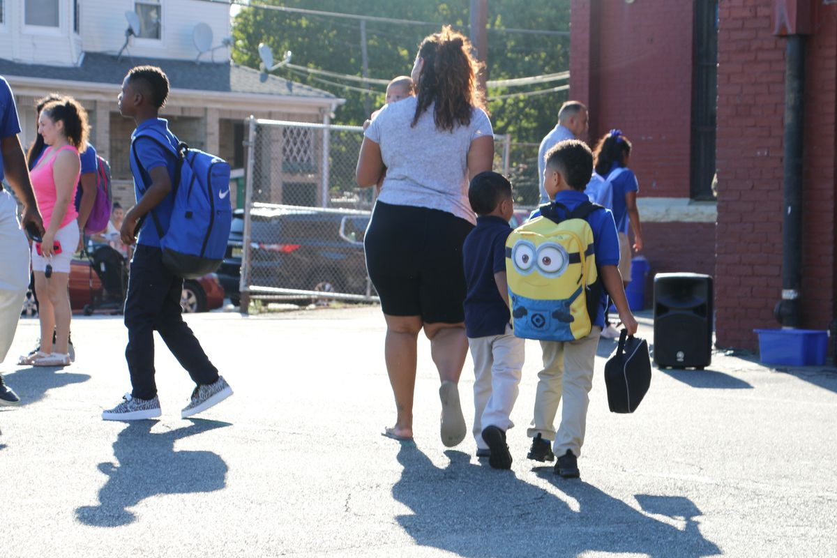 Students and parents walk in front of a red brick school on a sunny day.
