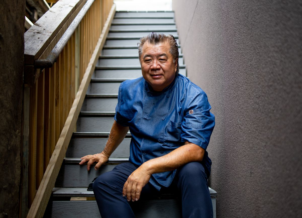 An older man wearing a blue chef's shirt sits on a staircase and smiles.