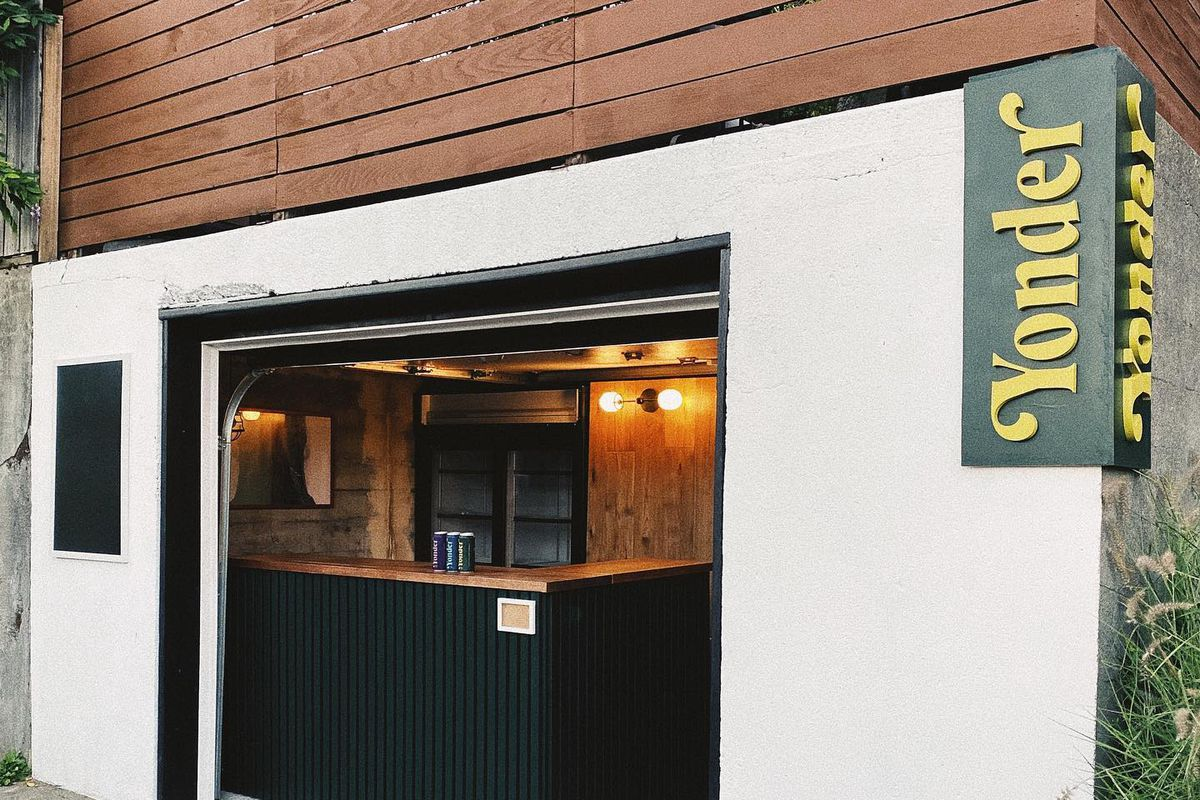 """The outside of Yonder Bar, with green trimming and the word """"Yonder"""" in yellow lettering, along with a small counter at the retail window"""