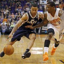 Utah Jazz guard Trey Burke (3) drives past Phoenix Suns guard Eric Bledsoe during the second half of an NBA basketball game on Saturday, Nov. 30, 2013, in Phoenix.