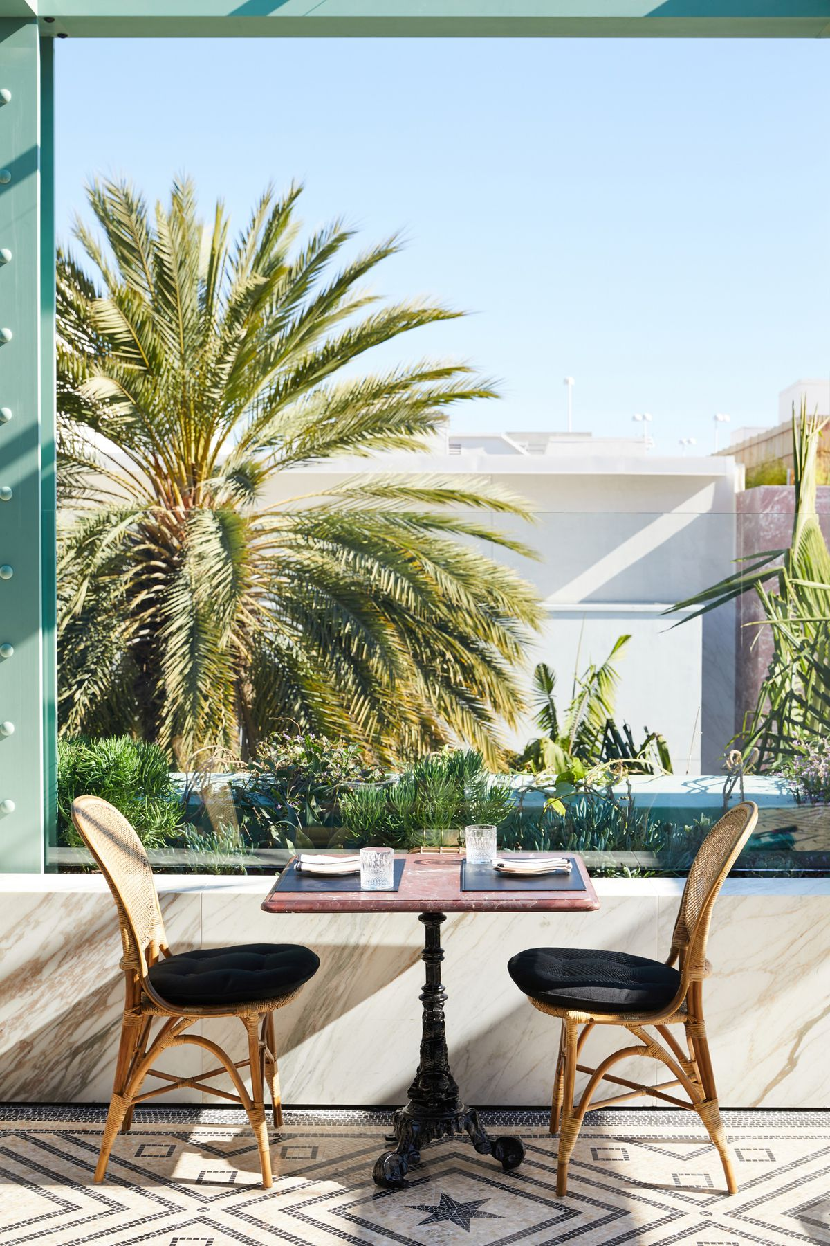 Seating at Gucci Osteria, Beverly Hills with wicker chairs and marble table