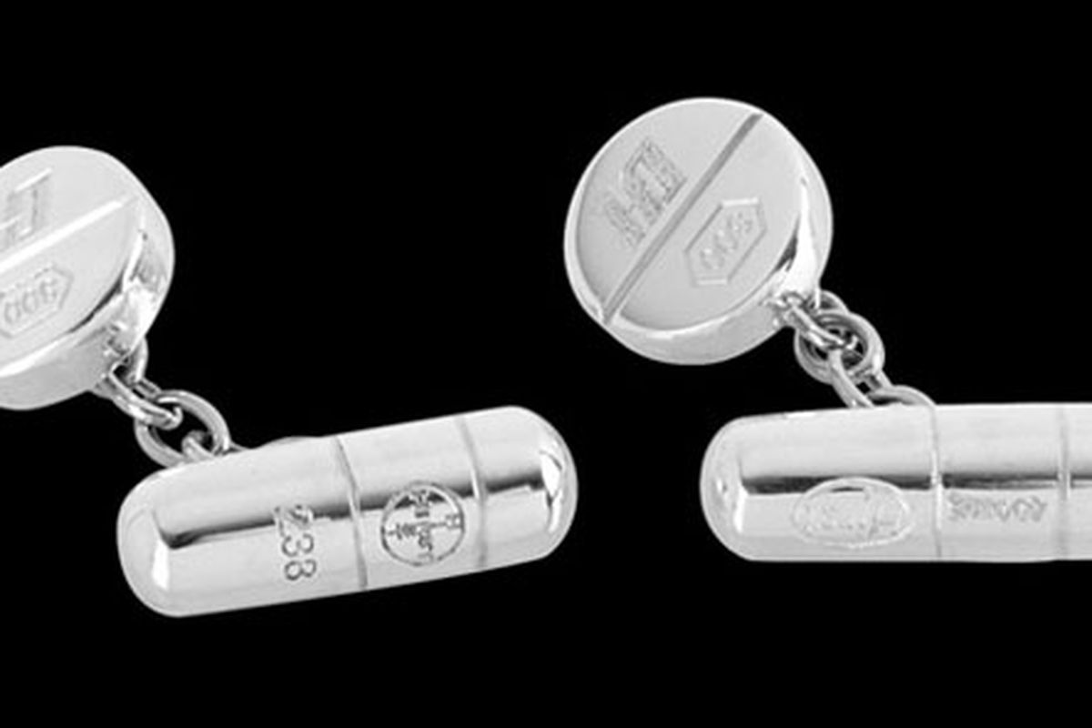 """Take two and call me in the morning: the king of animals in vats of formaldehyde branches out. Image via <a href=""""http://kronikle.kidrobot.com/damien-hirst-pill-cufflinks/"""">Kid Robot</a>."""