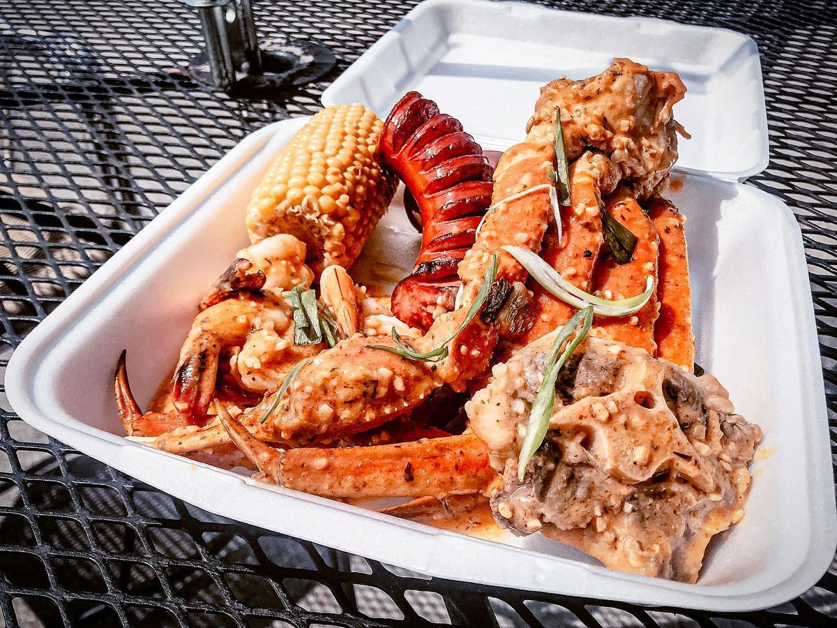 a box of boiled seafood with crab legs, a lobster tail and an oxtail