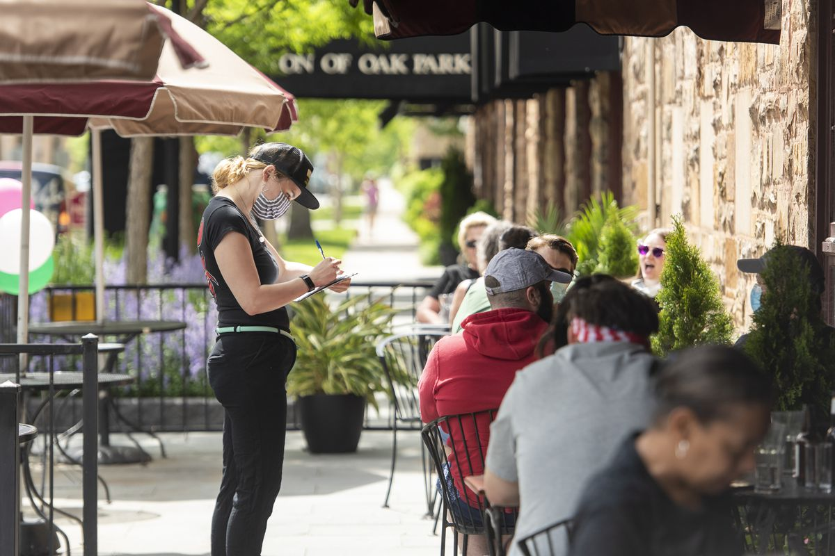 A server at Poor Phil's in Oak Park takes orders for patio dining in May.