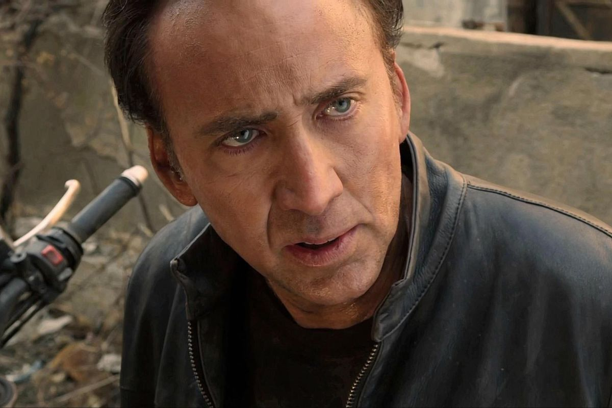 a close up of nicolas cage sitting on a motorcycle, looking stunned in ghost rider spirit of vengeance