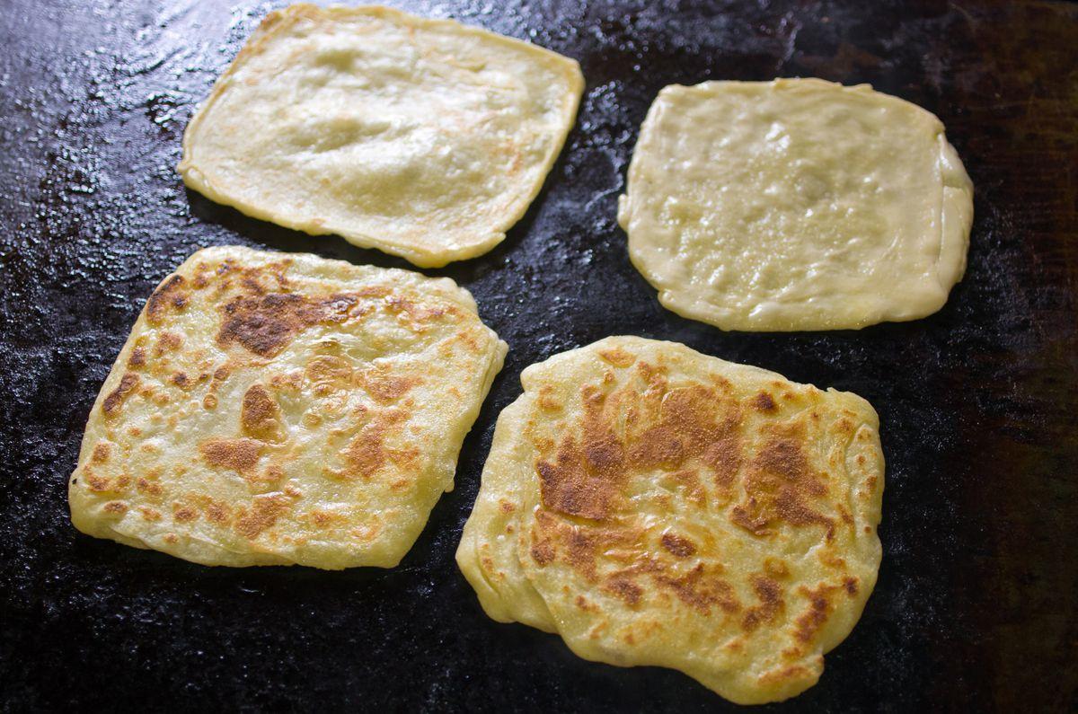 vier Quadrate von Msemen auf einem Kochfeld.