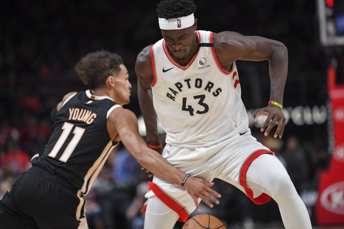 Toronto Raptors forward Pascal Siakam dribbles between his legs defended by Atlanta Hawks guard Trae Young during the first half at State Farm Arena.