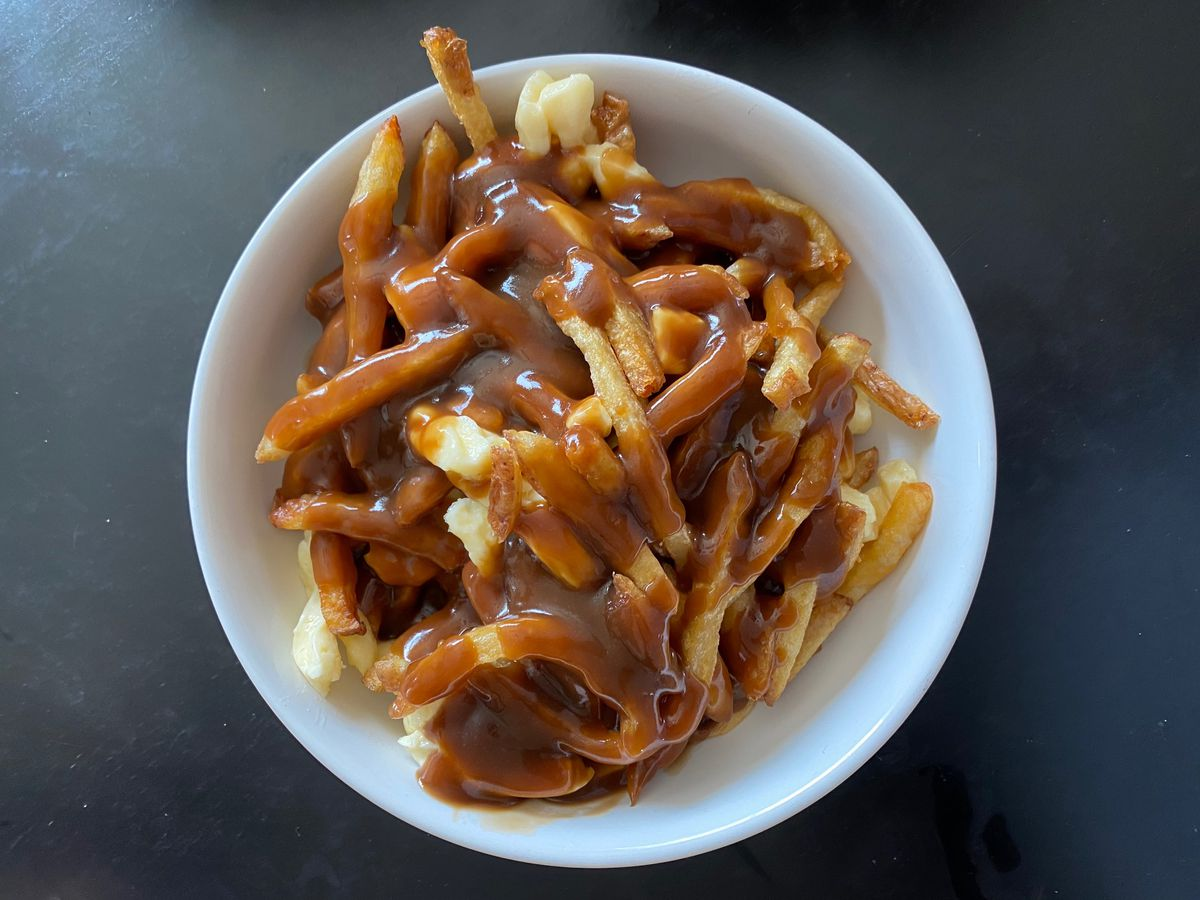 Poutine —fries covered in brown gravy and white cheese curds —on a white plate