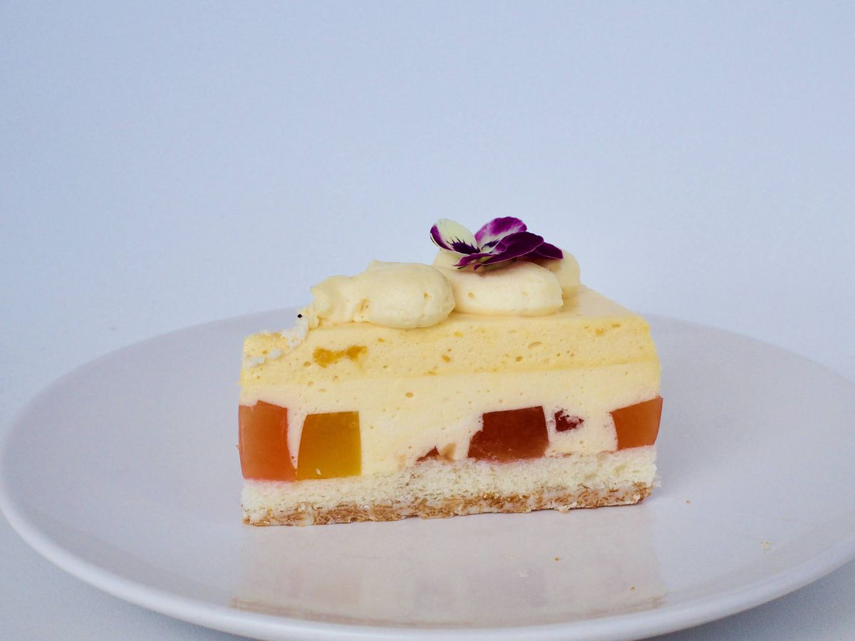 A slice of Jell-O cake on a plain plate, with bright blobs embedded in a creamy center, frosted topping and a bright flower for garnish