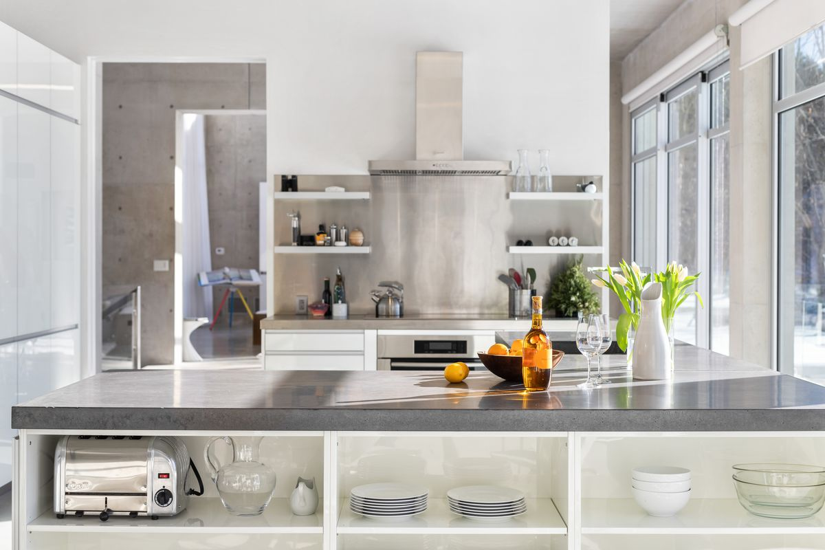 A modern kitchen sits in the center of an open floor plan. There are gray counters and open shelving.