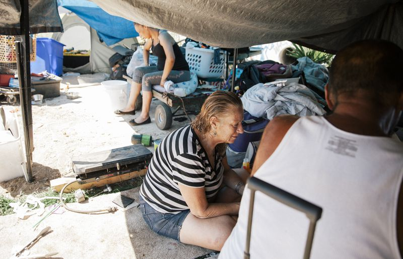 Two women and a man sit in the dirt under a black trap, surrounded by blankets, laundry, tents, and other supplies.