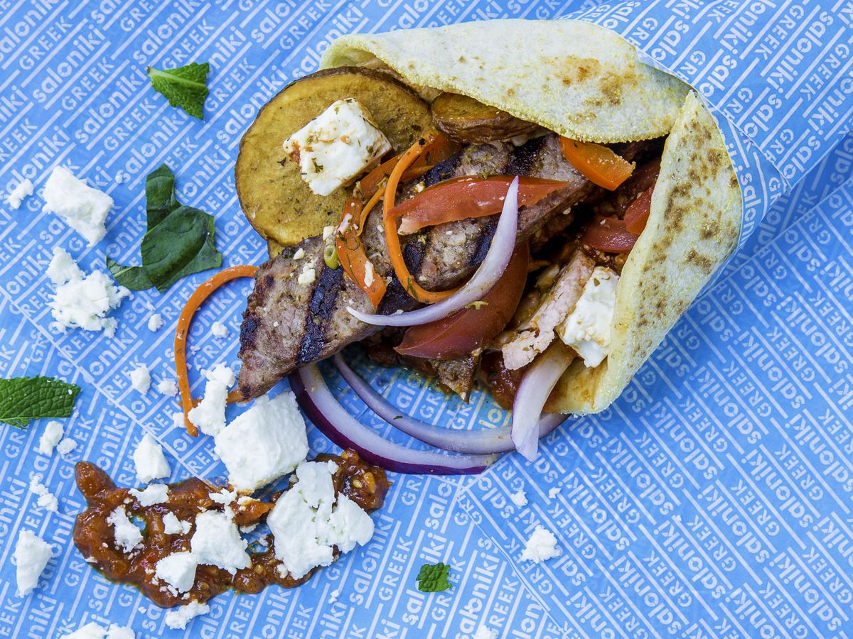 A pita sandwich filled with vegetables, chicken, and feta