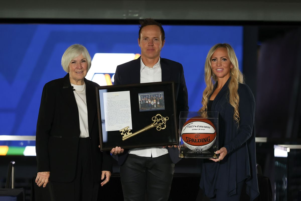 Gail Miller, Qualtrics CEO Ryan Smith and his wife, Ashley Smith, pose for a photograph at Vivint SmartHome Arena in Salt Lake City on Wednesday, Oct. 28, 2020. The group announced Wednesday that Miller is selling the Utah Jazz to Smith.
