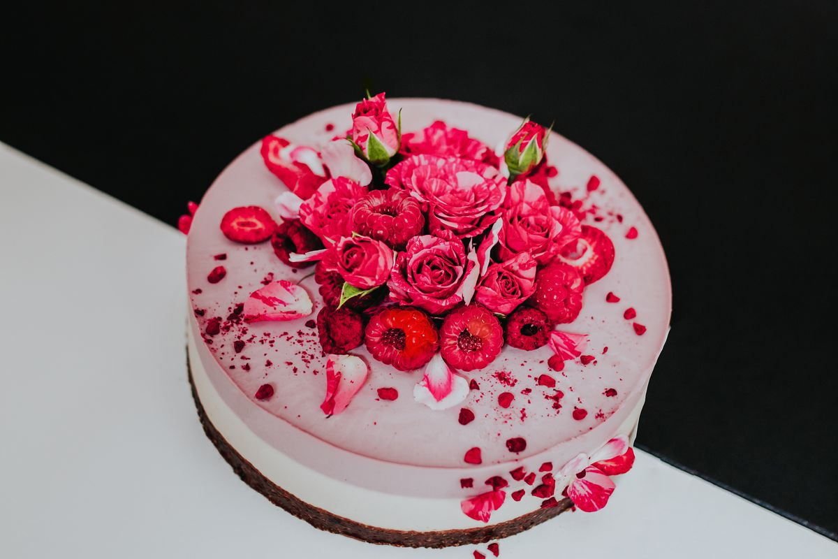A pink cake topped with raspberries and roses.