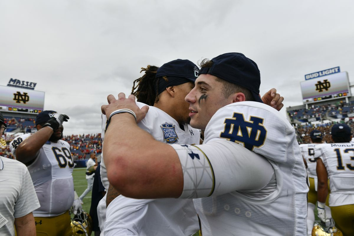 Notre Dame Fighting Irish wide receiver Chase Claypool and Notre Dame Fighting Irish quarterback Ian Book embrace after the Camping World Bowl between the Notre Dame Fighting Irish and the Iowa State Cyclones on December 28, 2019, at Camping World Stadium in Orlando, FL.