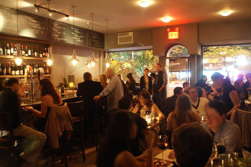 A dining room full of people with wine lining the wall