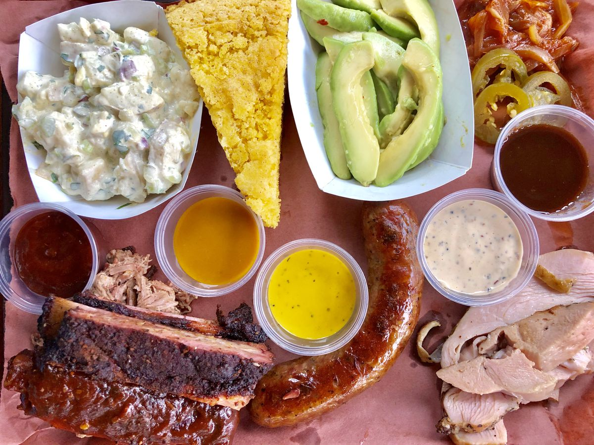 An overhead photo of a tray of barbecue, including ribs, a sausage, turkey, cornbread, pulled pork, pickled avocado, potato salad, and barbecue onions