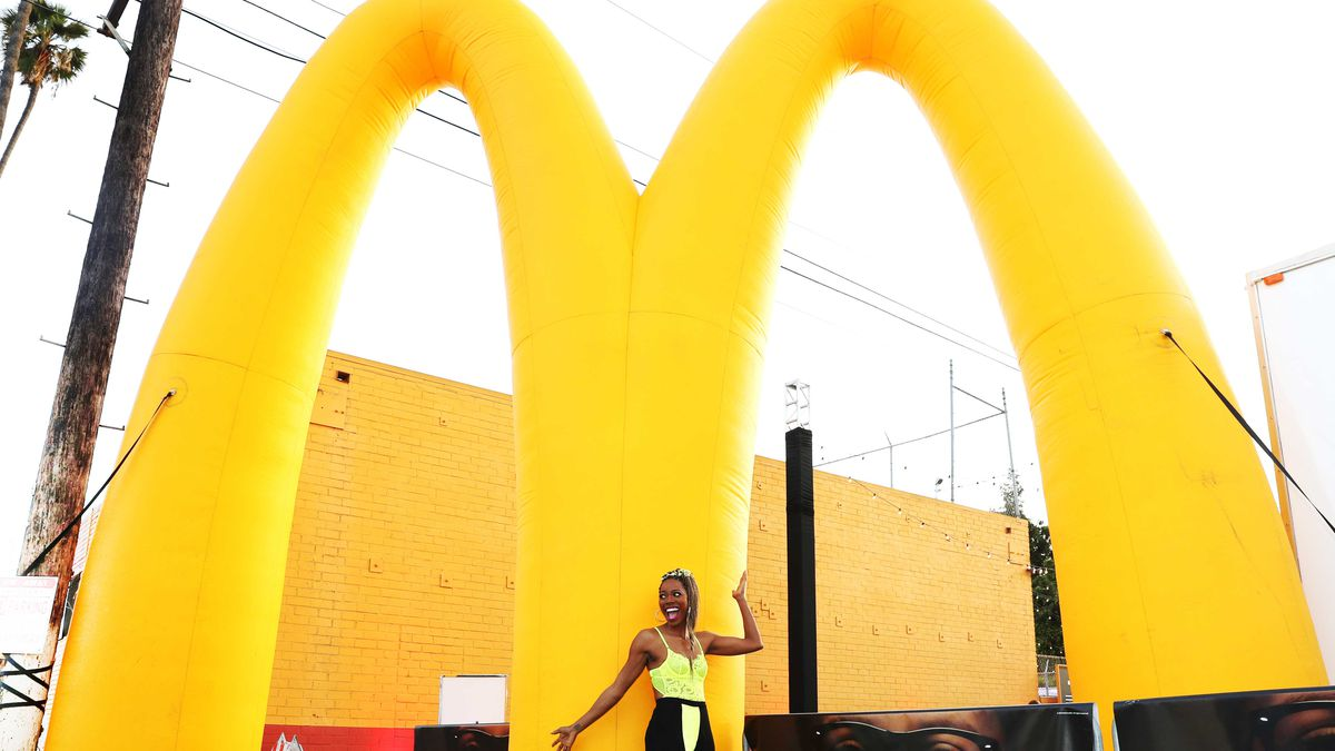 Yvonne Orji poses in front of a giant inflatable McDonald's golden arches outdoors in Los Angeles.