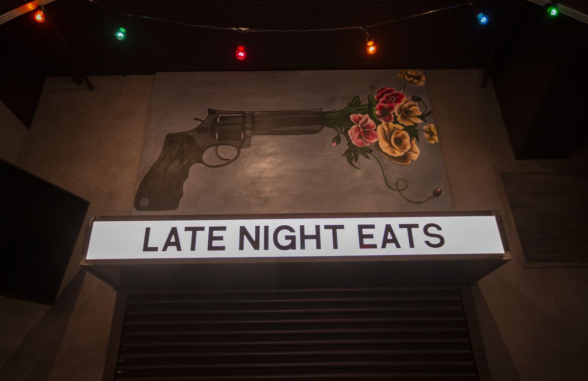 """A dark bar space with a mural of a gun with flowers coming out of it and a sign that reads """"late night eats."""""""