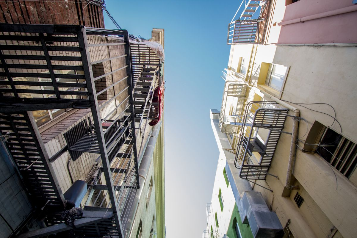 Looking up towards blue sky, surrounded by buildings, with a low perspective