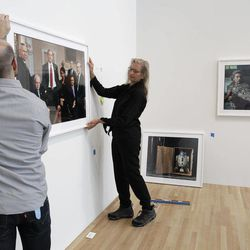 """Annie Leibovitz, right, helps Zak Kelley, of Columbus, hang one of her photographic prints before the opening of her exhibition at the Wexner Center for the Arts Friday, Sept. 21, 2012, in Columbus, Ohio. Leibovitz's exhibition features work from her """"Master Set,"""" an authoritative edition of 156 images."""