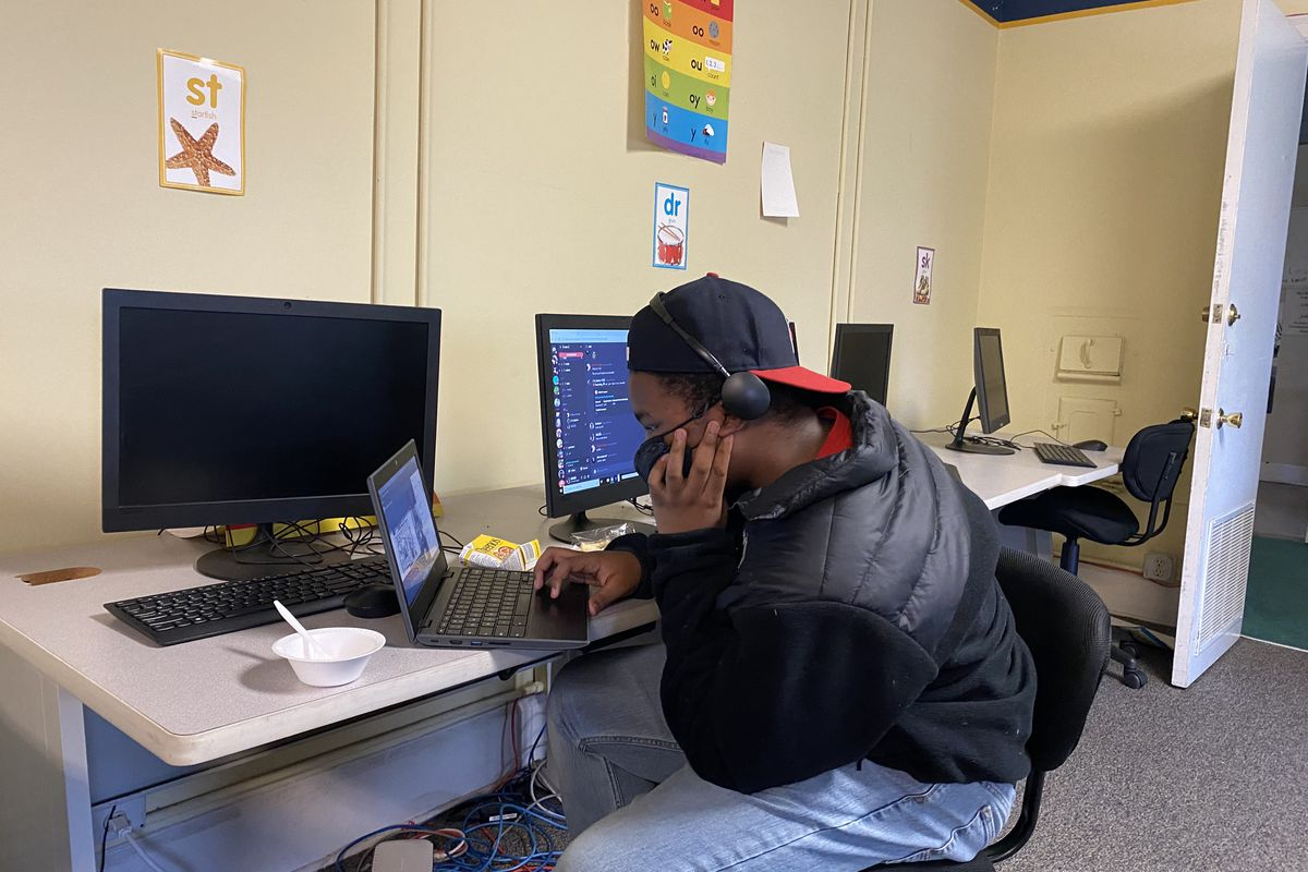 Student looks at a laptop while sitting at a table with desktop monitors