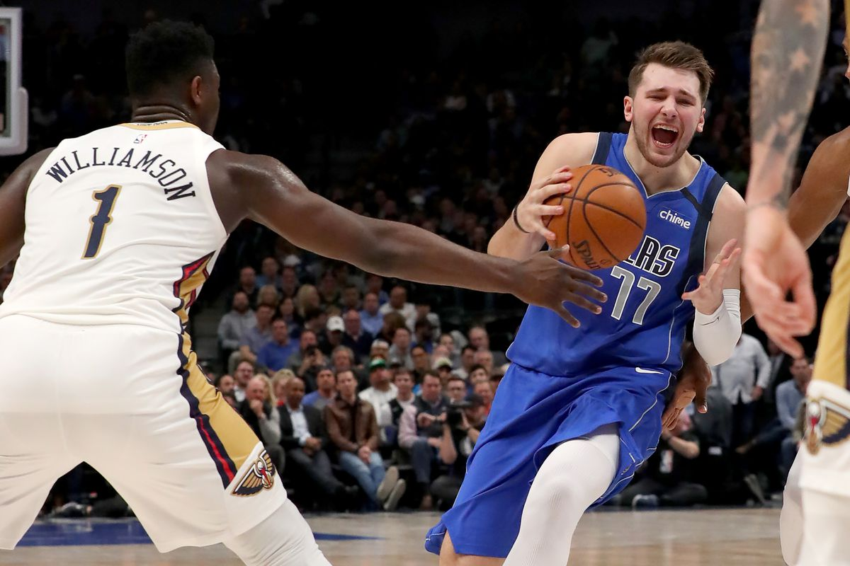 Luka Doncic of the Dallas Mavericks drives to the basket against Zion Williamson of the New Orleans Pelicans and Lonzo Ball of the New Orleans Pelicans in the second quarter at American Airlines Center on March 04, 2020 in Dallas, Texas.