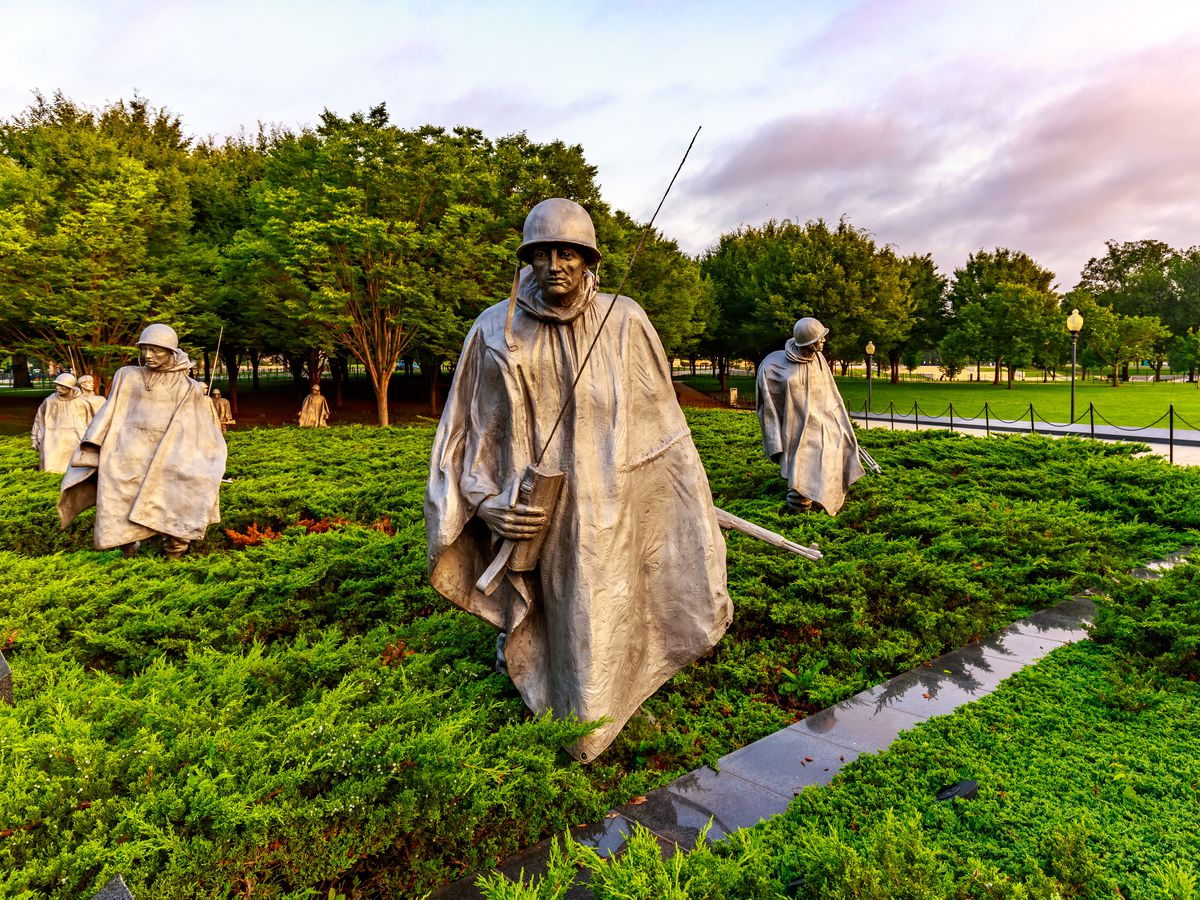 Four stainless steel statues of soldiers in a field of juniper bushes.
