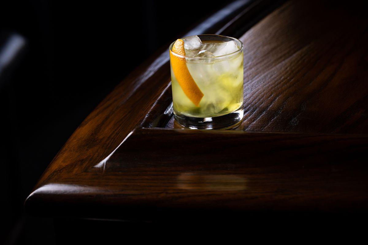 A dim corner of a bartop with a light green and yellow cocktail and orange peel.