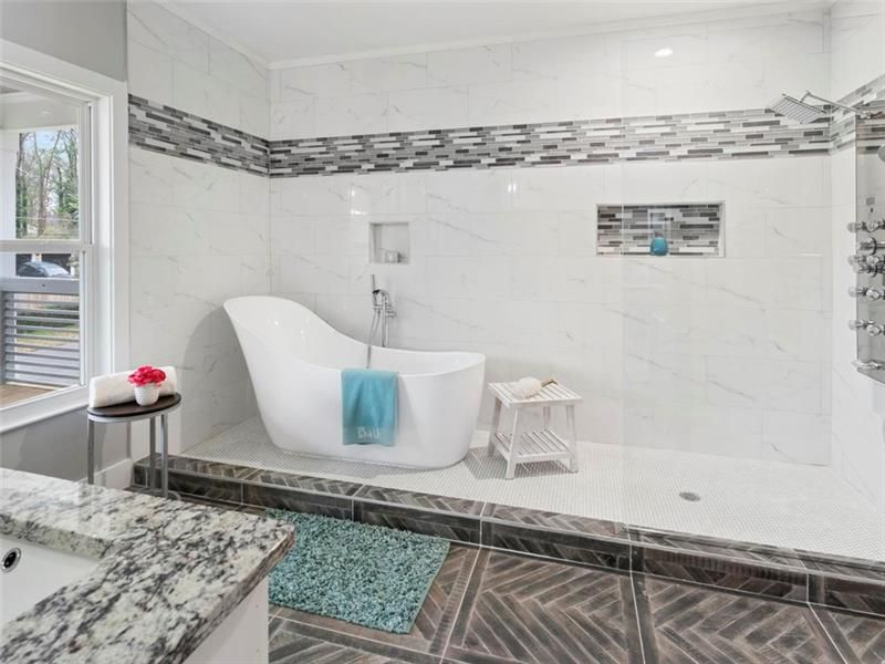 A white bathroom with a tub in the shower.