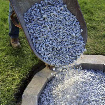 Man Fills Fire Pit With Gravel