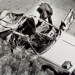 A police officer searches Mark Hofmann's car after a bomb exploded, injuring Hofmann on Oct. 16, 1985.