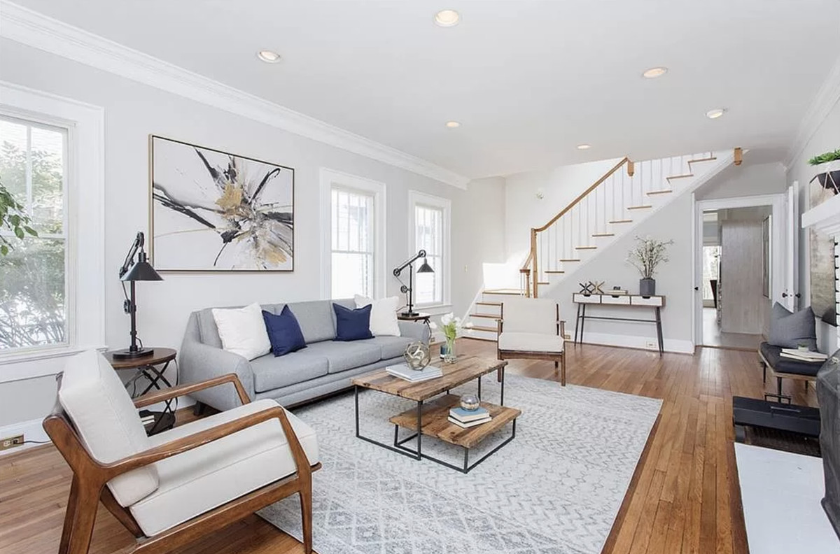 White living room with hardwood floors, couch, chairs, coffee table and area rug.