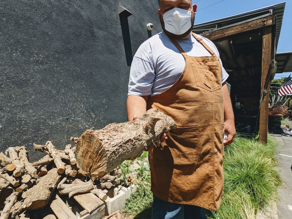 Rudy Suazo holding up a log of peach wood outside Maple Block Barbecue in Culver City.