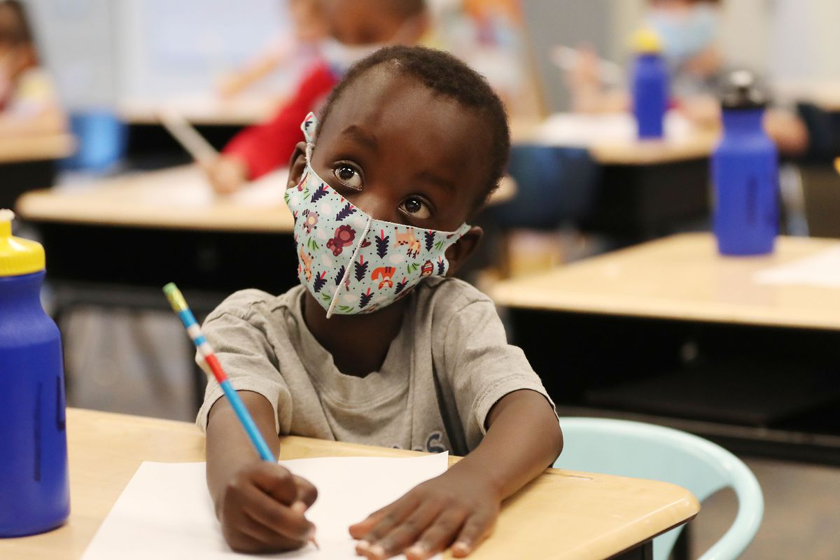 Kindergartner Isaac Nshuti wears a mask as he does an assignment at Woodrow Wilson Elementary School in Salt Lake City.