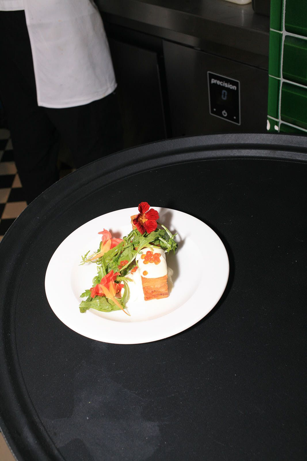 A tray with a white plate containing Sessions Arts Club's fried potato, eel, and creme fraiche
