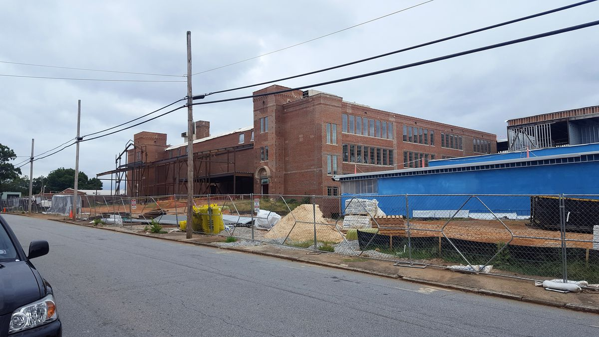 The blue structure is at the right of the old red-brick building, which is undergoing restoration.