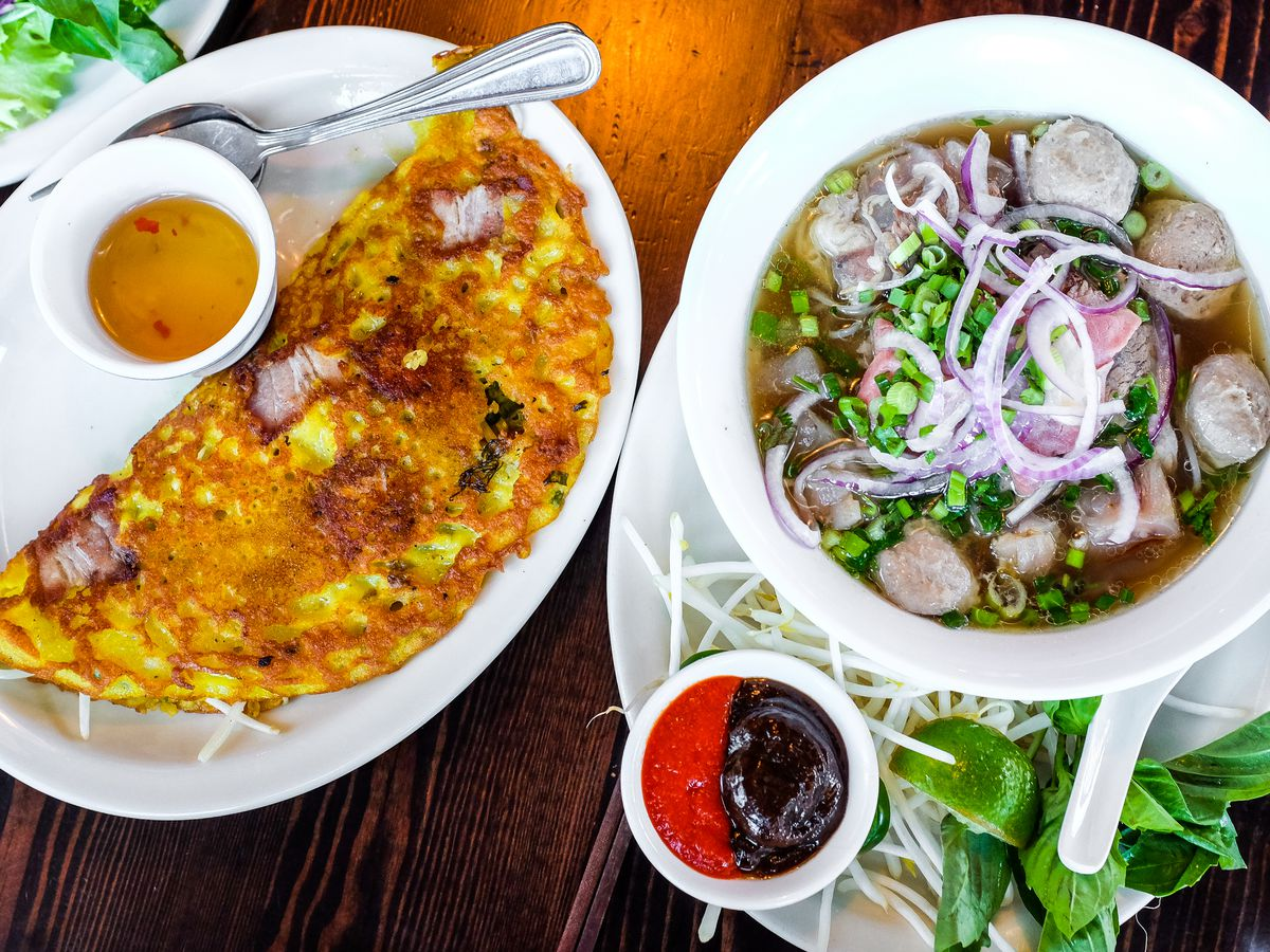A crepe lightly browned next to a bowl of pho, stuffed with noodles and dumplings.