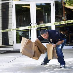 Visalia Police Officer Bob Douglas removes evidence after a shooting that killed Bishop Clay Sannar of the Church of Jesus Christ of Latter-Day Saints Sunday, Aug. 29, 2010 in Visalia, Calif.