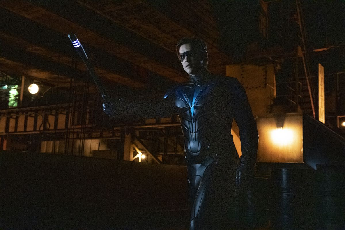 Brenton Thwaites as Robin in Titans season 3, holding up a glowing baton in a warning gesture