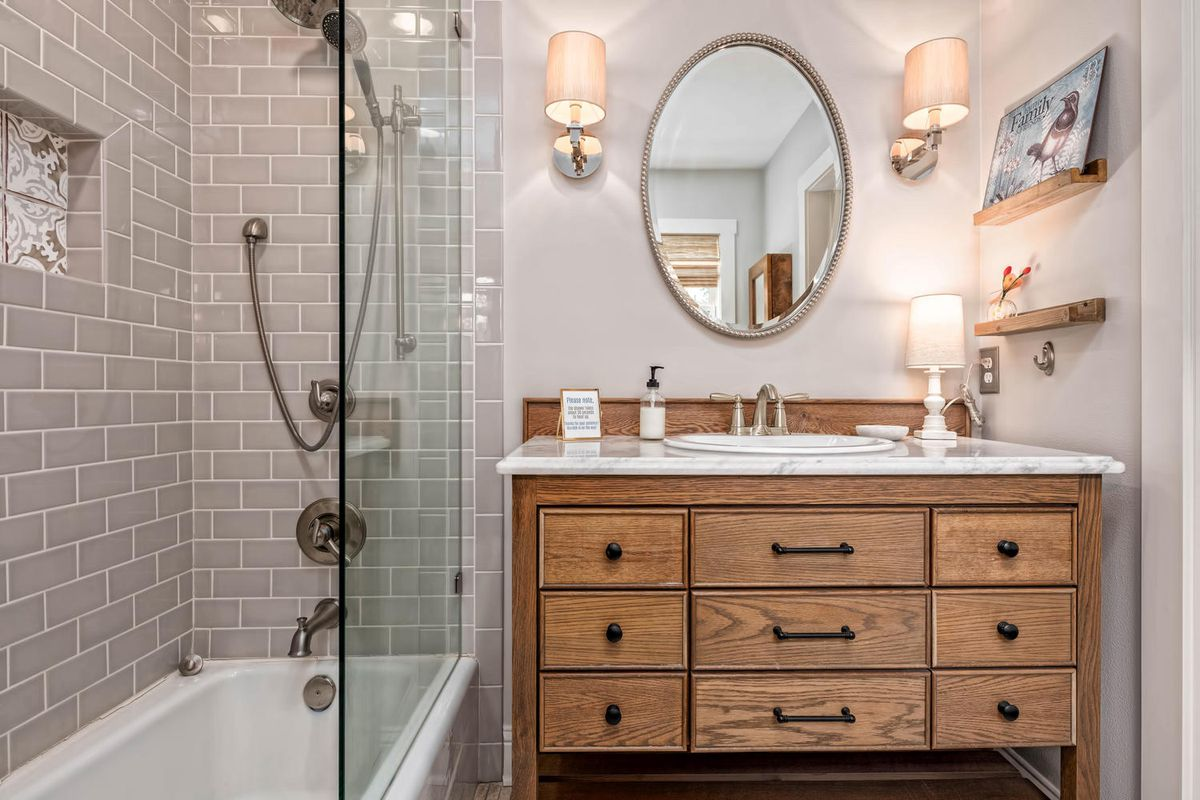 A bathroom has a wooden vanity, one mirror, and gray shower.