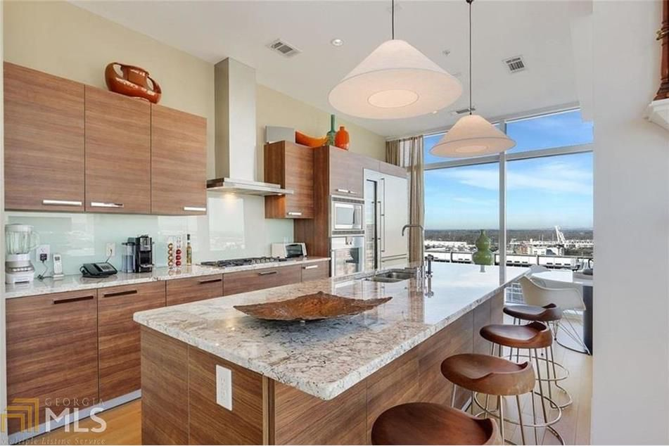 A kitchen with brown cabinets and stools.