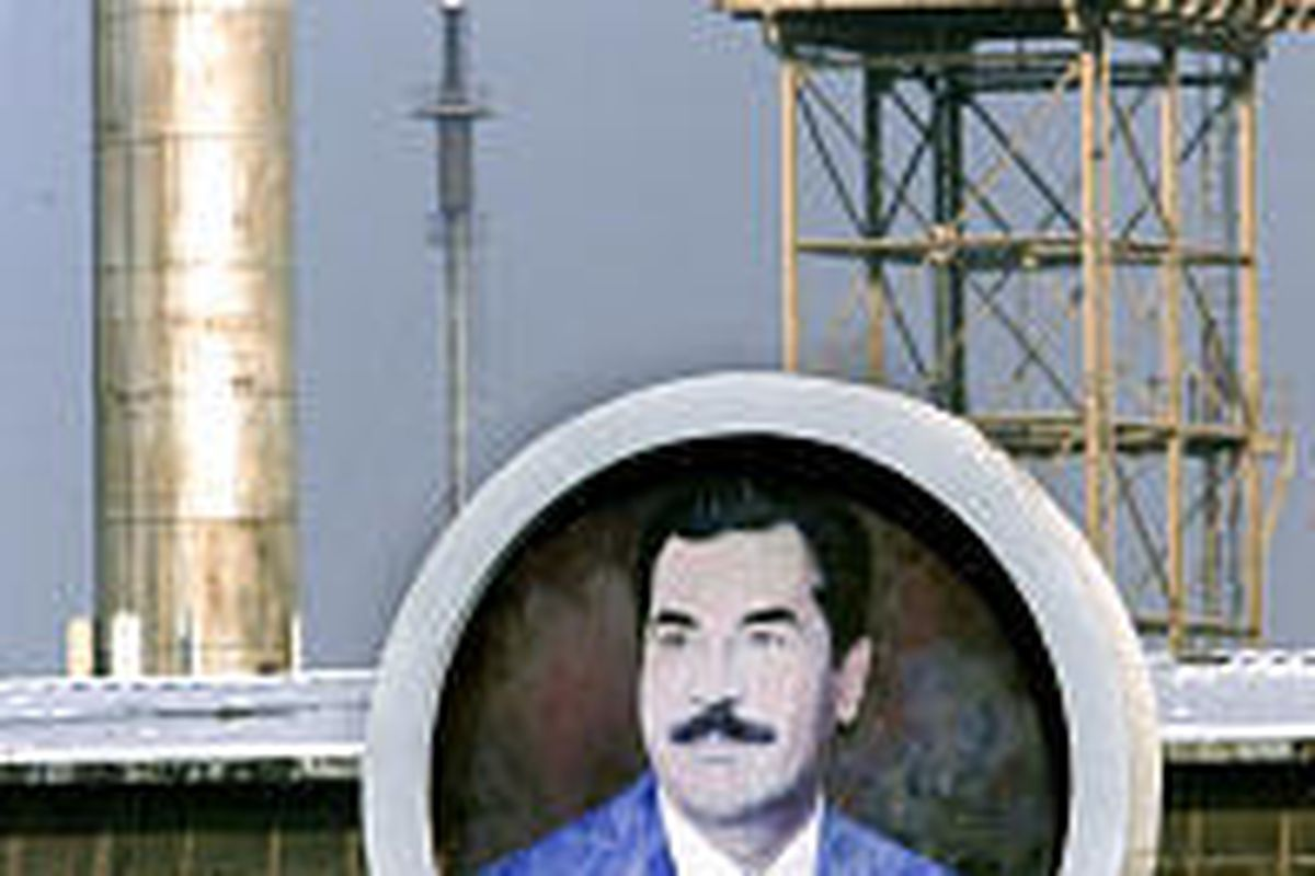 A poster of Saddam Hussein at a Baghdad refinery in 1998. Reconstruction plans face obstacles.