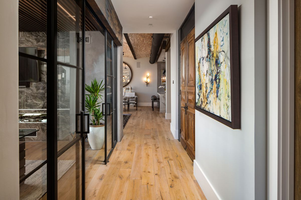 A long hallways with wide plan wood floors and big walnut doors at right with an office at left.