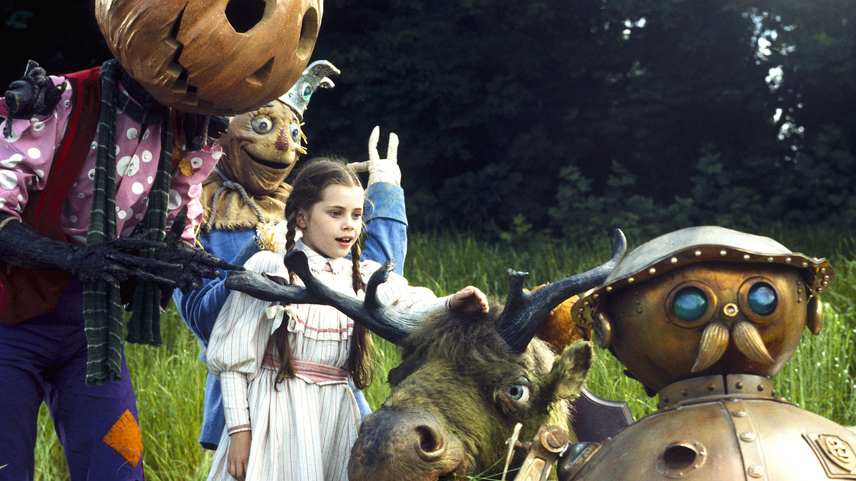 Dorothy, with the Scarecrow and a pumpkin-headed man, reaches out towards a horned, green creature.